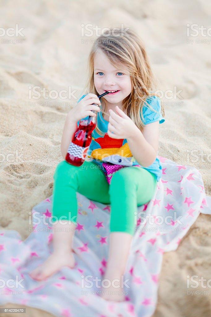 Glückliches Mädchen am Strand trinkt Saft stock photo