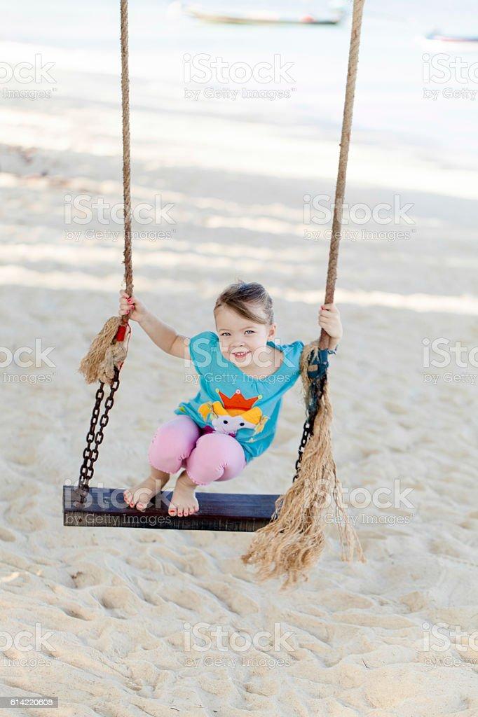 Glückliches Mädchen schaukelt am Strand stock photo