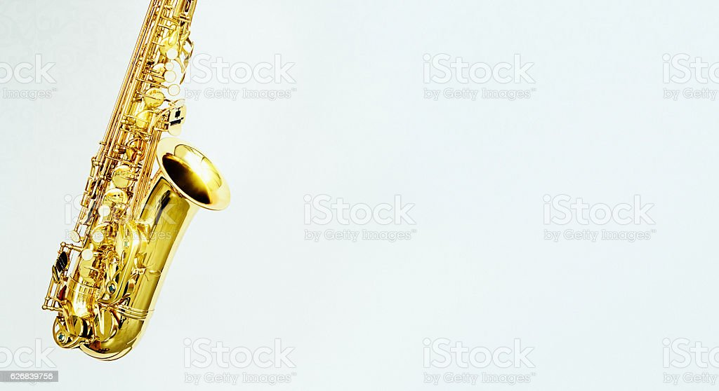 Gleaming golden alto sax on gray with copy space stock photo