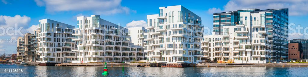 Gleaming white modern apartment buildings waterfront homes panorama Copenhagen Denmark stock photo