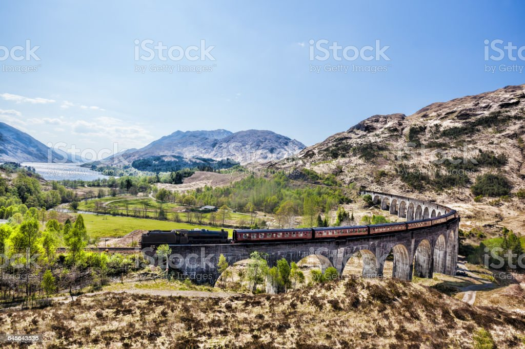 Glenfinnan Railway Viaduct in Scotland with the Jacobite steam train against sunset over lake stock photo