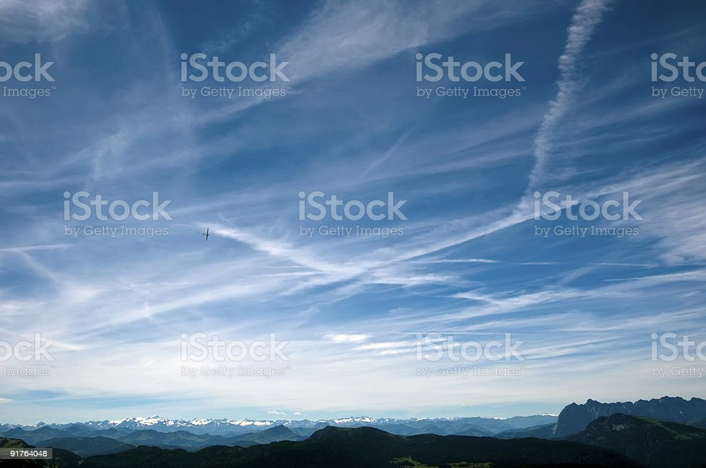 glider and contrails over the Alps royalty-free stock photo