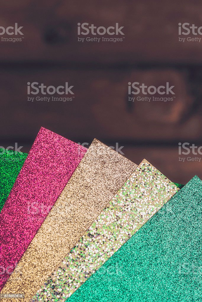 Glitter card in a variety of colors against rustic wood stock photo