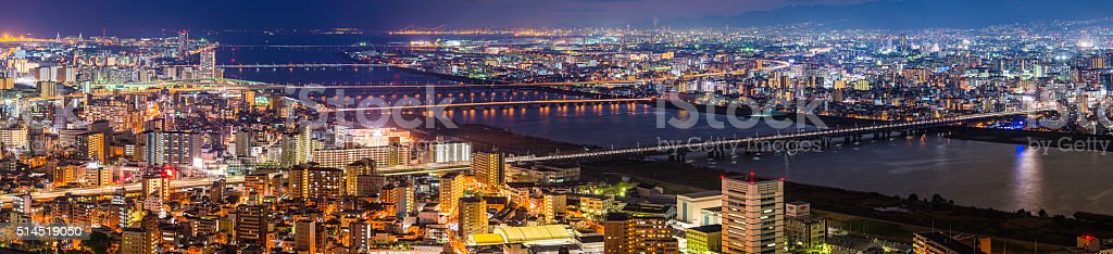 Glittering cityscape bridges illuminated at night Yodo River Osaka Japan stock photo