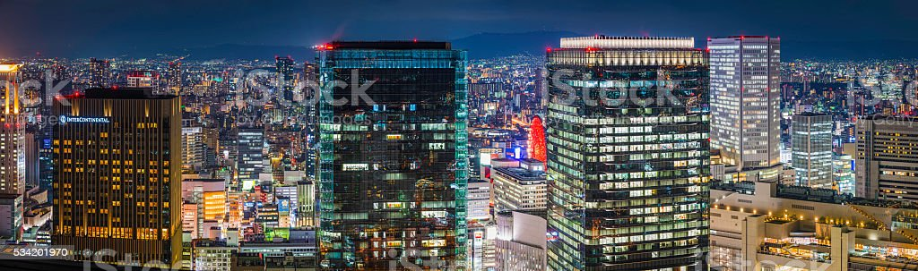 Glittering skyscrapers illuminated in futuristic neon cityscape panorama Osaka Japan stock photo