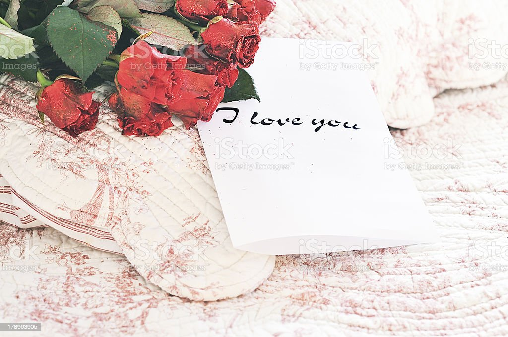 Glittery roses and love letter on the bed royalty-free stock photo