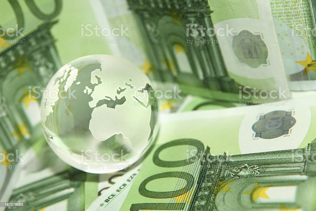 Global finance and money represented by Earth globe on banknotes royalty-free stock photo