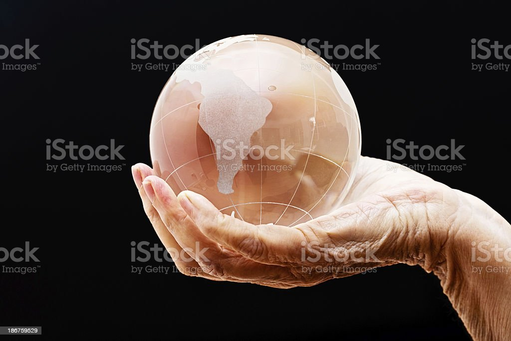 Global fortune telling: wrinkled hand holds crystal ball representing Earth royalty-free stock photo
