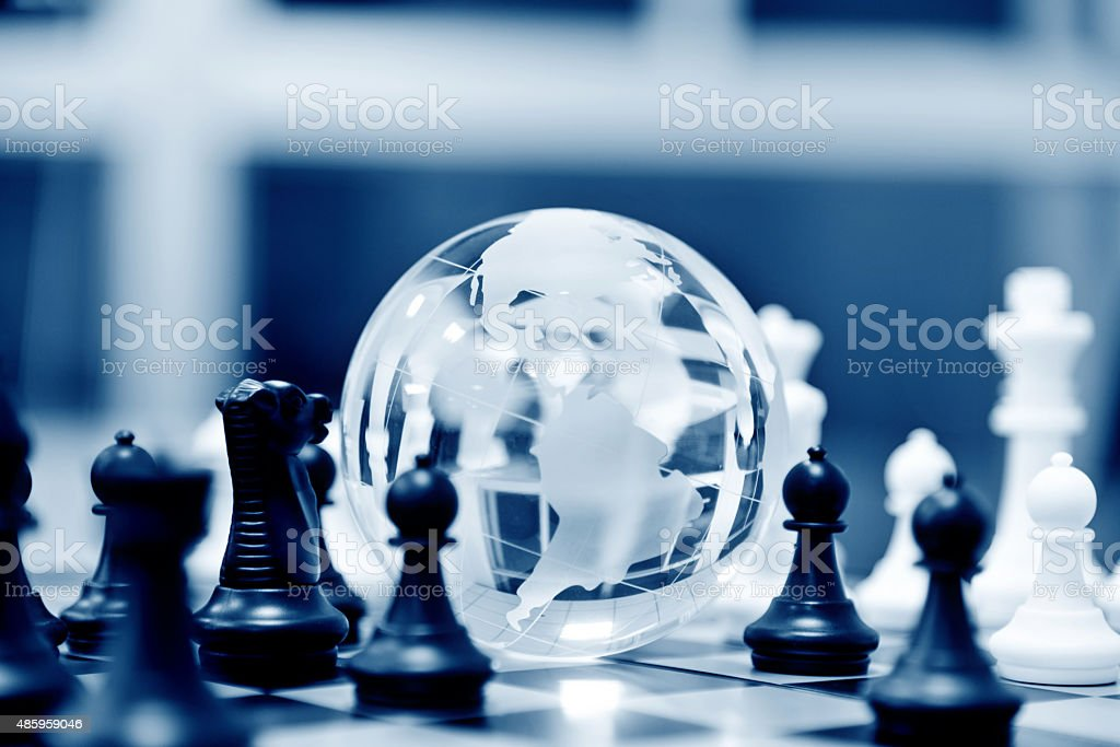 Globe and chess pieces stock photo