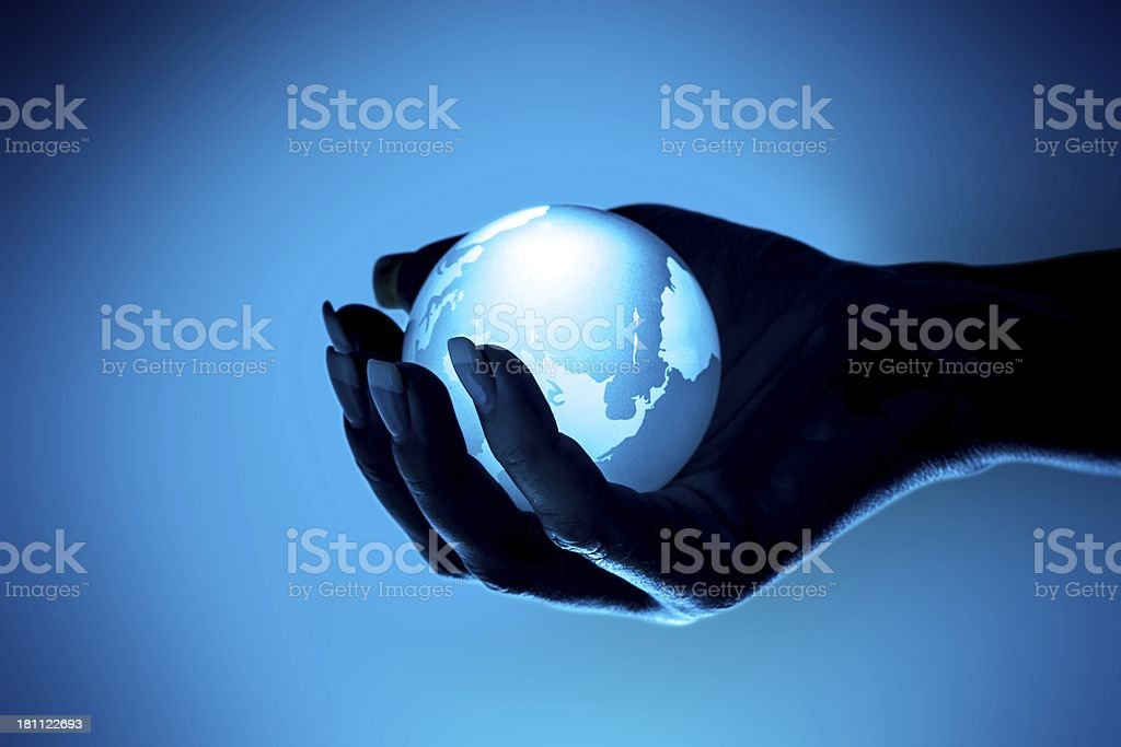 Globe in woman hand on blue background royalty-free stock photo
