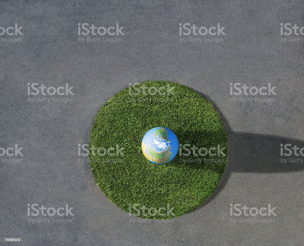 Globe on circle of grass on pavement outdoors royalty-free stock photo