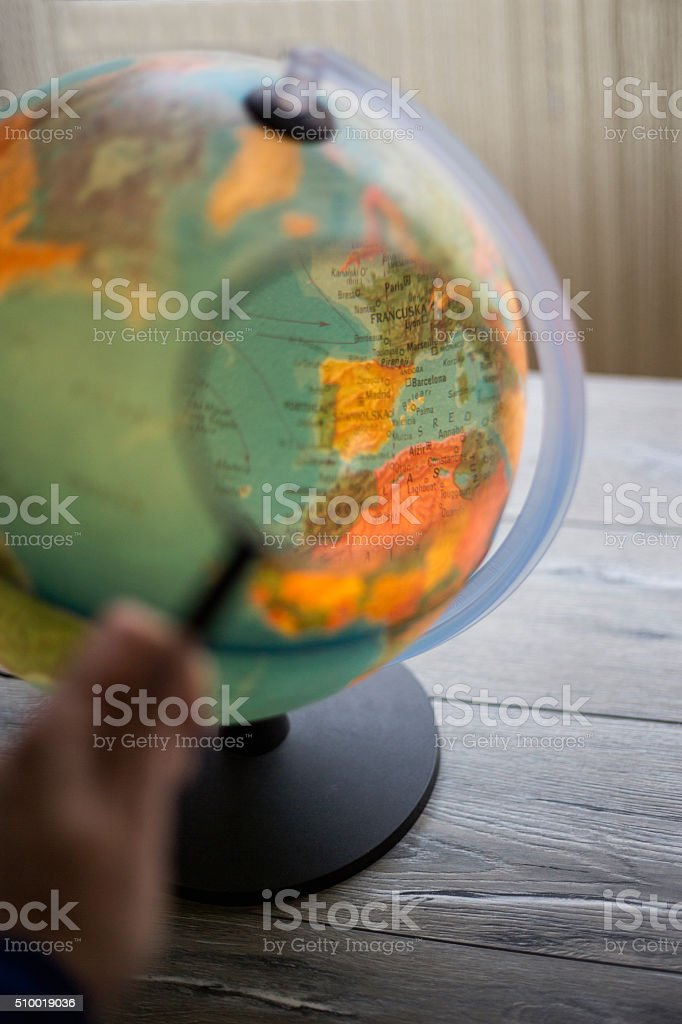 globe sphere under a magnifying glass stock photo