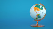 Globe with geographical map on blue background.