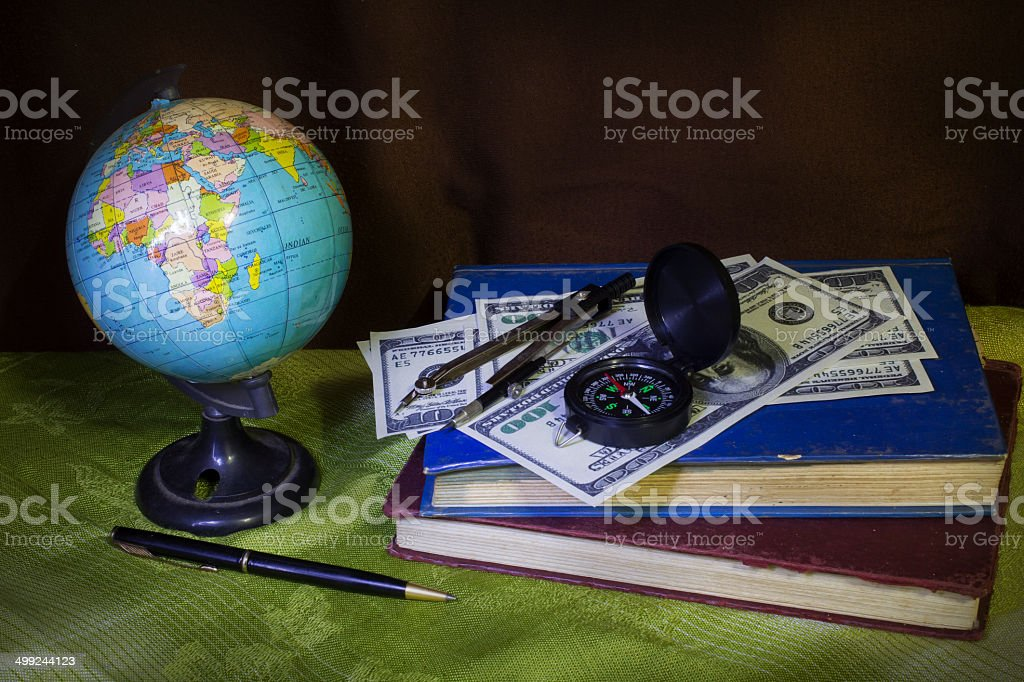 Globe with money,compass and book. royalty-free stock photo