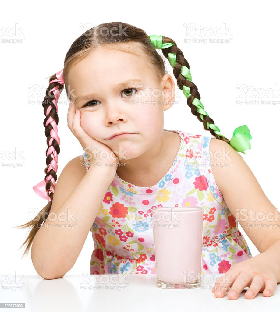 Gloomy little girl doesn't want to drink milk stock photo