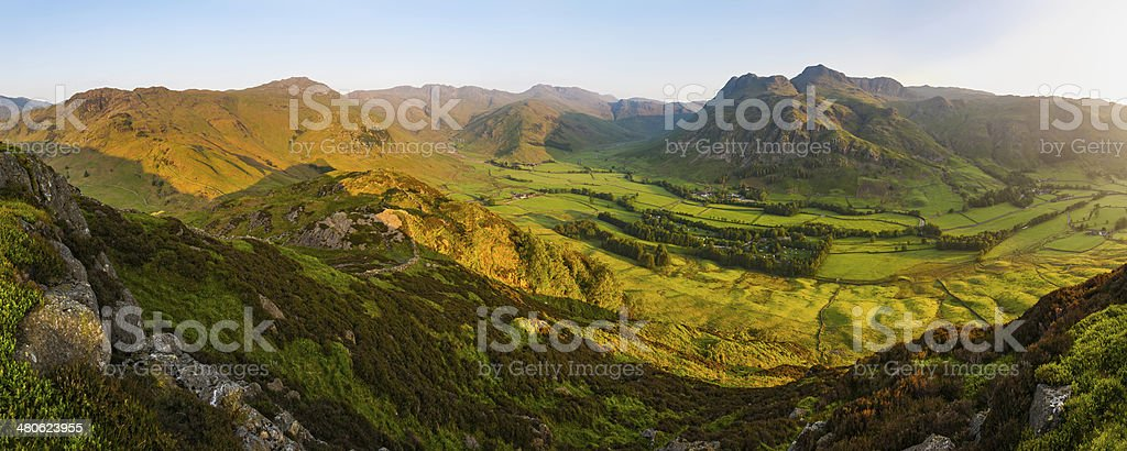 Glorious summer sunrise idyllic green mountain valley rocky peaks panorama stock photo