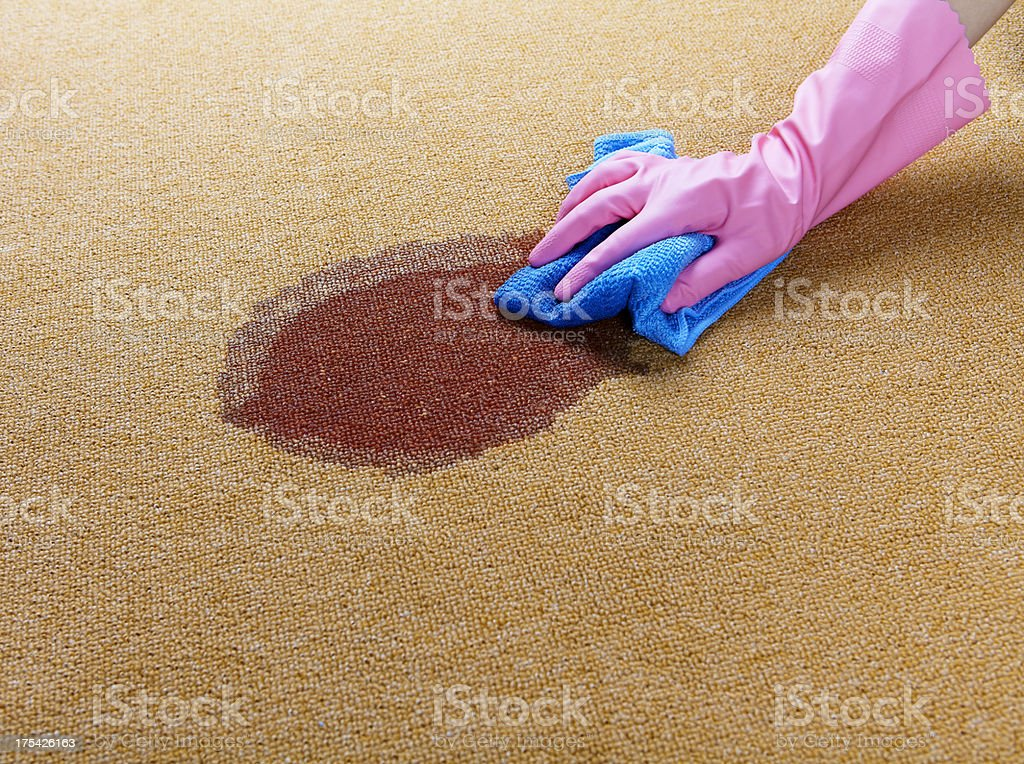 Gloved hand cleaning a wet spot on floor stock photo