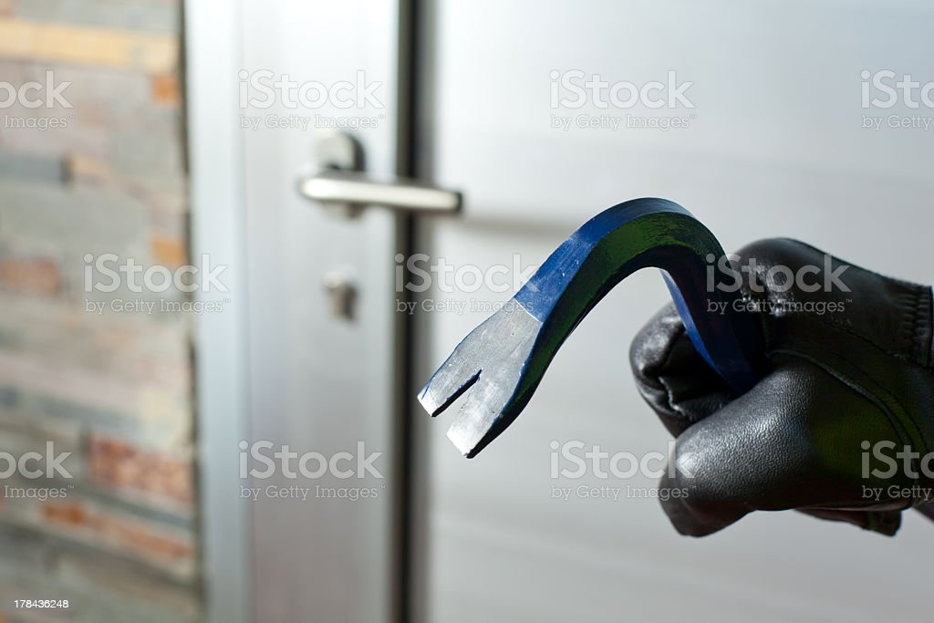 A gloved hand holding a crow bar in front of a door stock photo