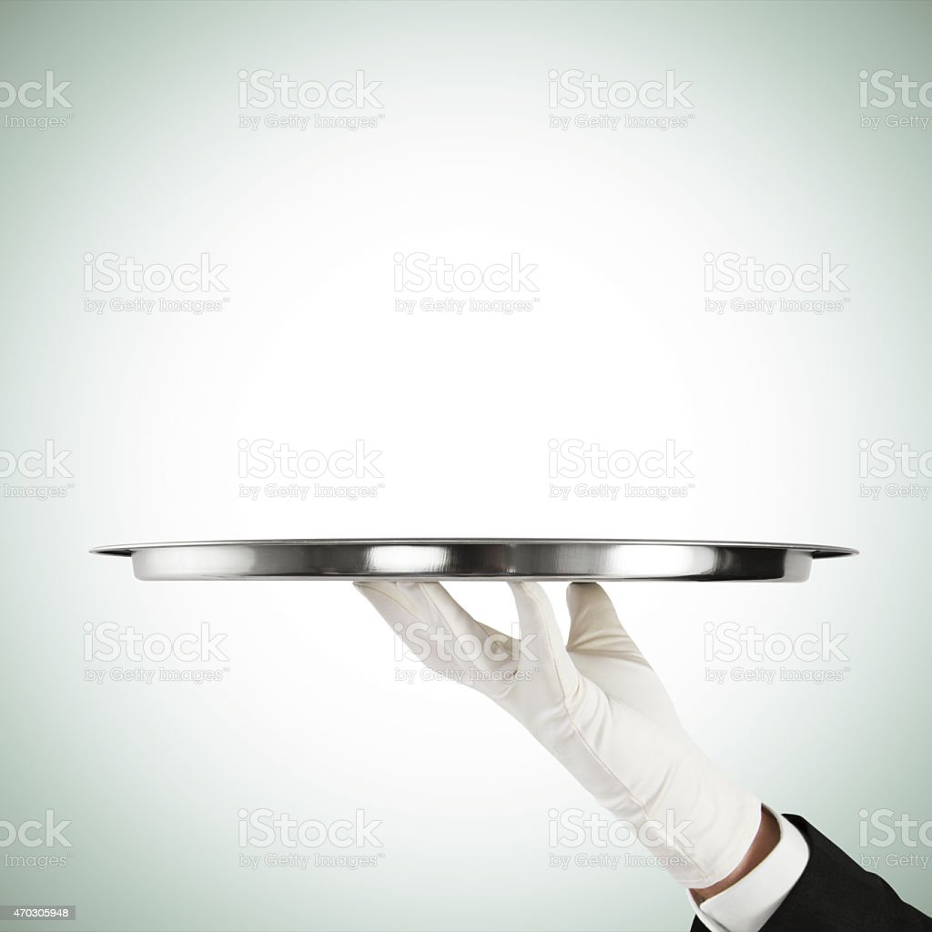 A gloved hand holding a silver serving tray stock photo