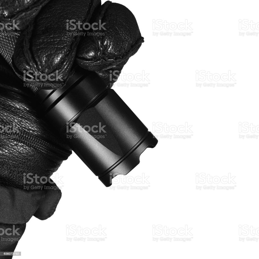 Gloved Hand Holding Tactical Flashlight, Bright, Strike Bezel, Isolated Closeup stock photo