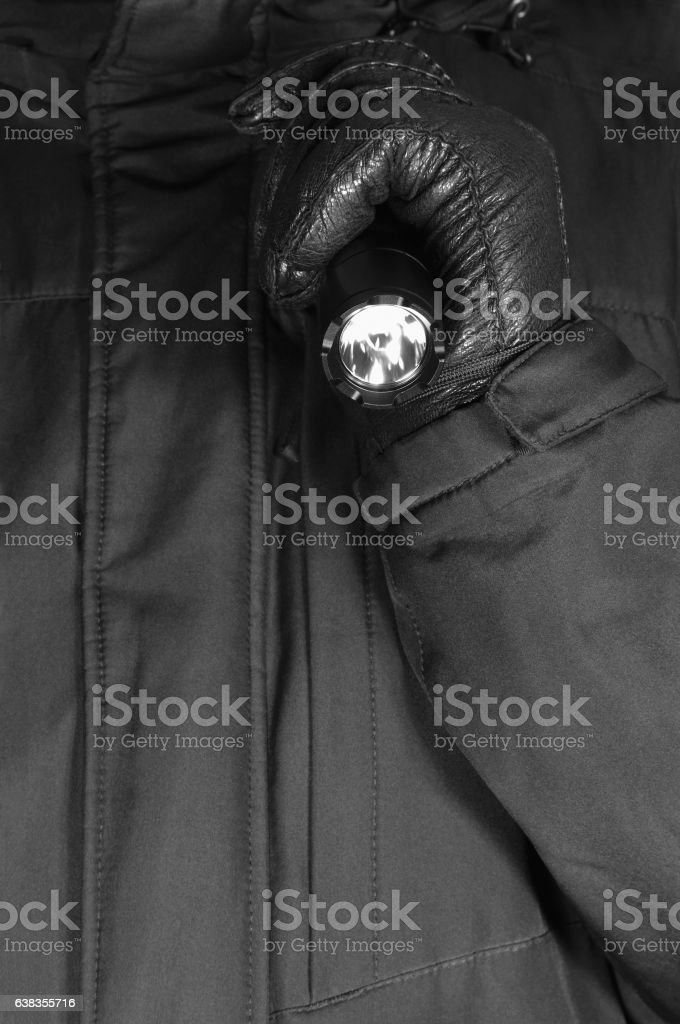Gloved Hand Holding Tactical Flashlight stock photo