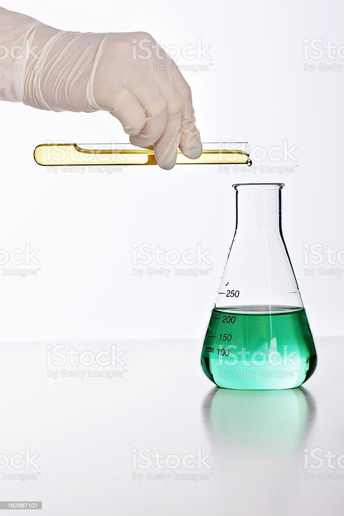 Gloved hand pours golden liquid into flask of green fluid royalty-free stock photo