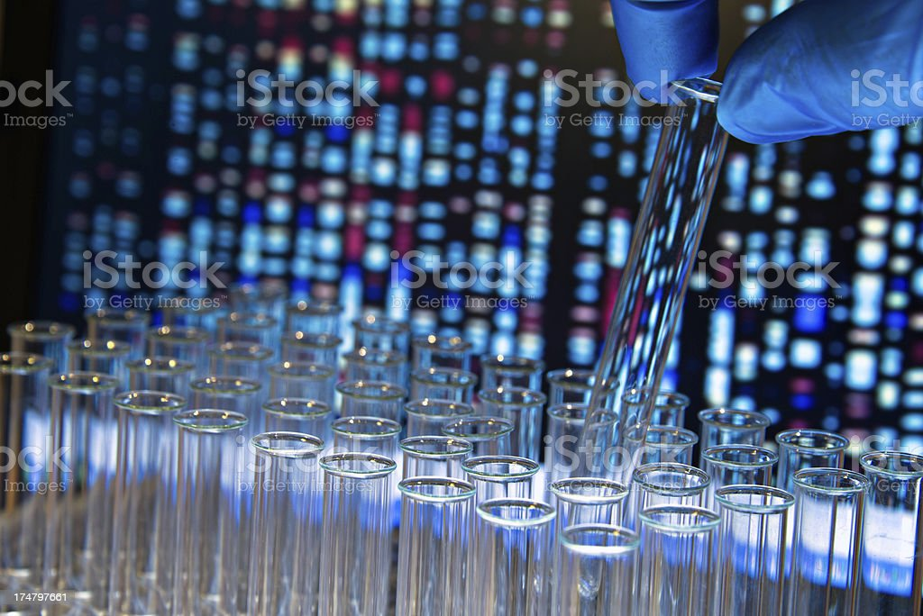 Gloved hand removes test tube against gene chart background royalty-free stock photo
