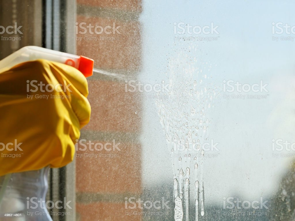 Gloved hand spraying cleaning solution on window stock photo