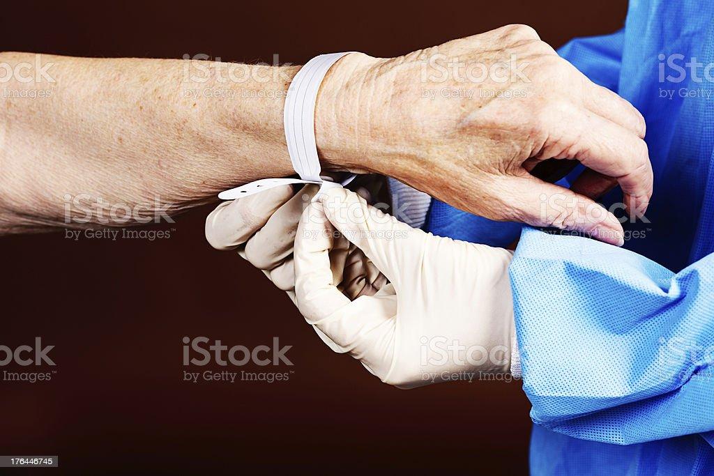 Gloved hands attach hospital identity bracelet to elderly, wrinkled arm stock photo