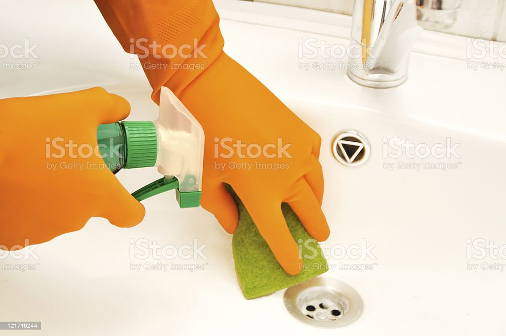 Gloved hands cleaning a drain in a bathroom royalty-free stock photo