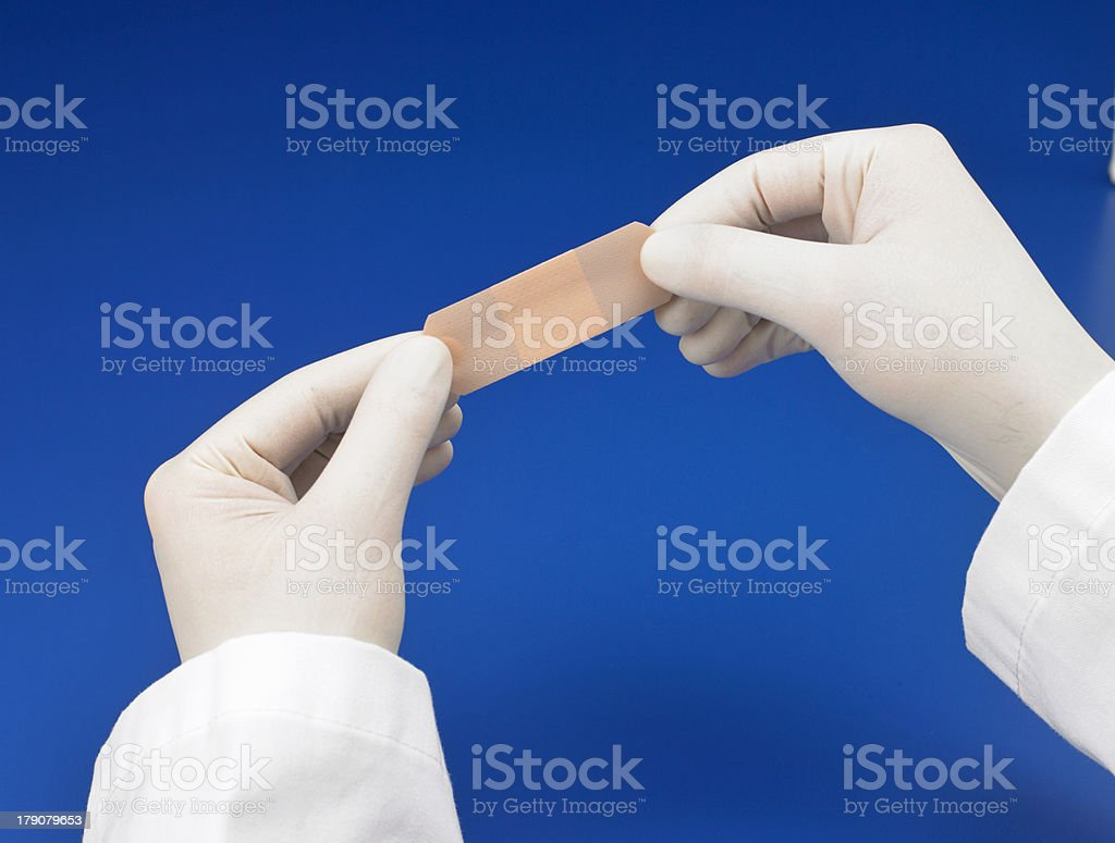 Gloved hands holding a bandaid stock photo