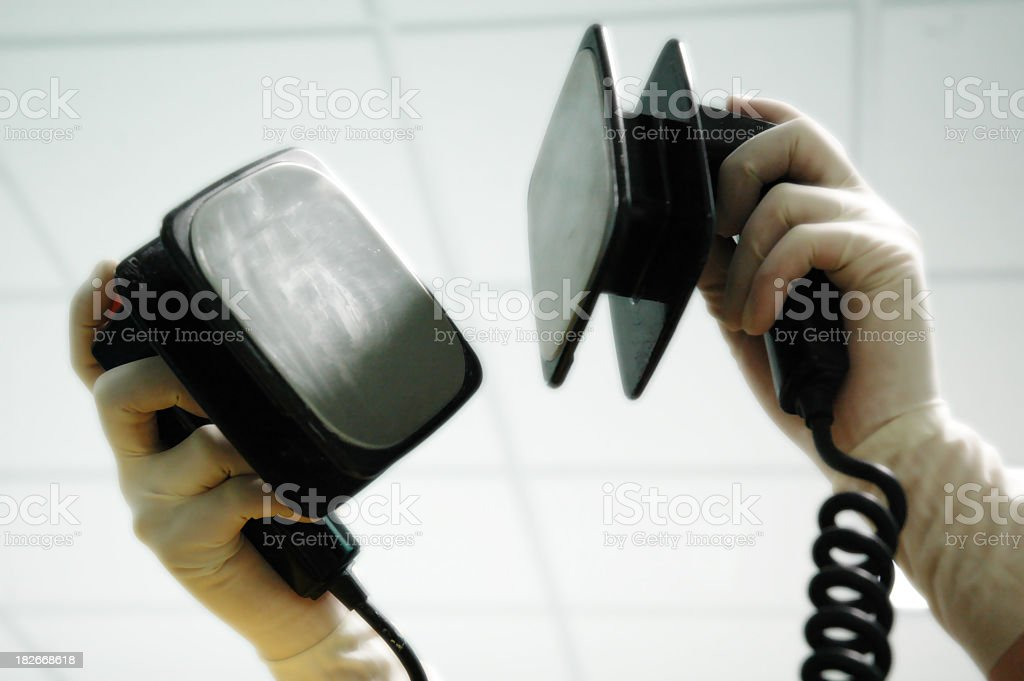 Gloved hands holding a defibrillator in the air stock photo
