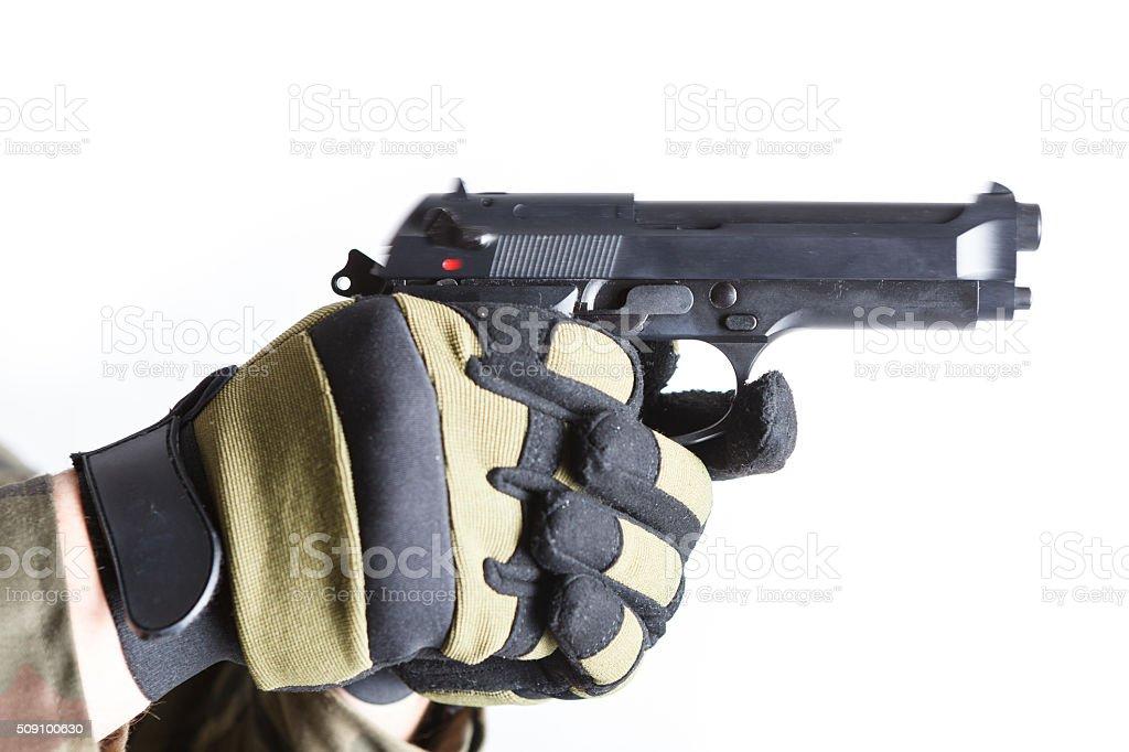 Gloved hands holding a gun stock photo