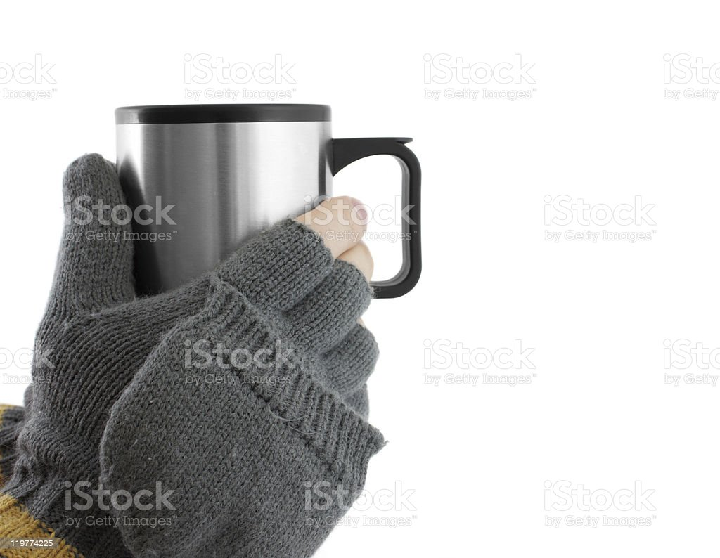 Gloved hands holding a travel mug stock photo