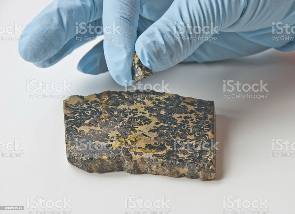 Gloved hands holding uraninite stock photo