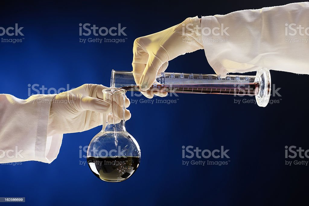 Gloved hands pour liquid from beaker into lab flask royalty-free stock photo