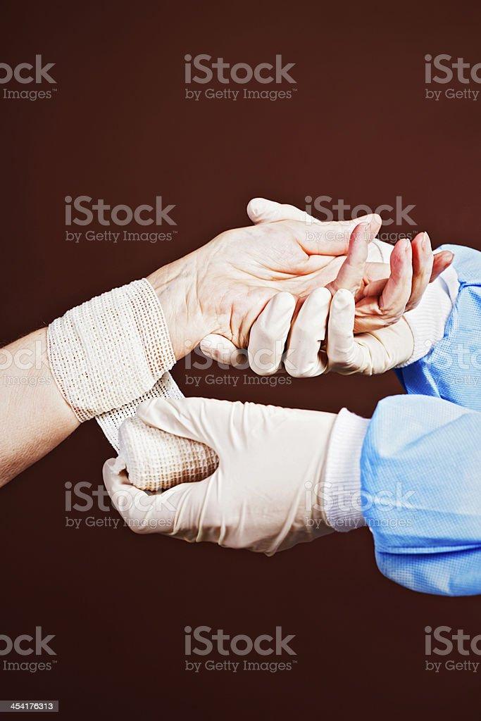 Gloved professional hands bandage elderly female arm royalty-free stock photo