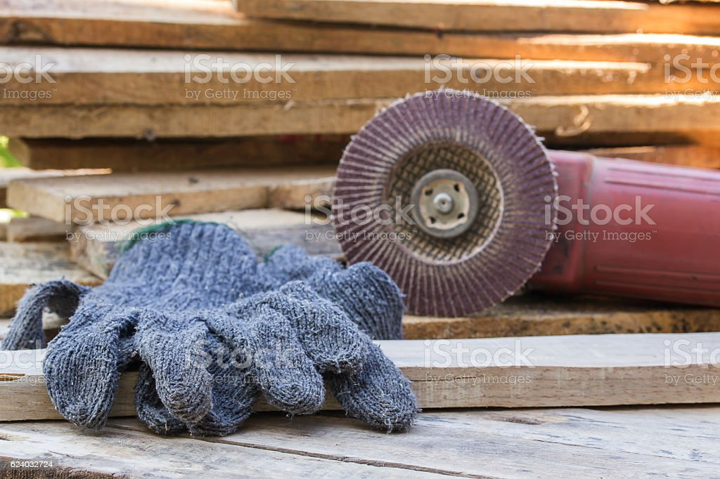 Gloves and electric sandpaper tool on wooden table stock photo