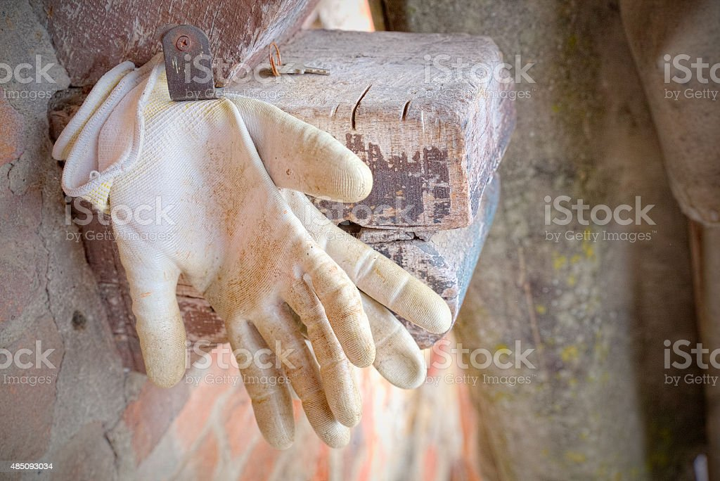 Gloves of an artisan or peasant hanging on the nail stock photo