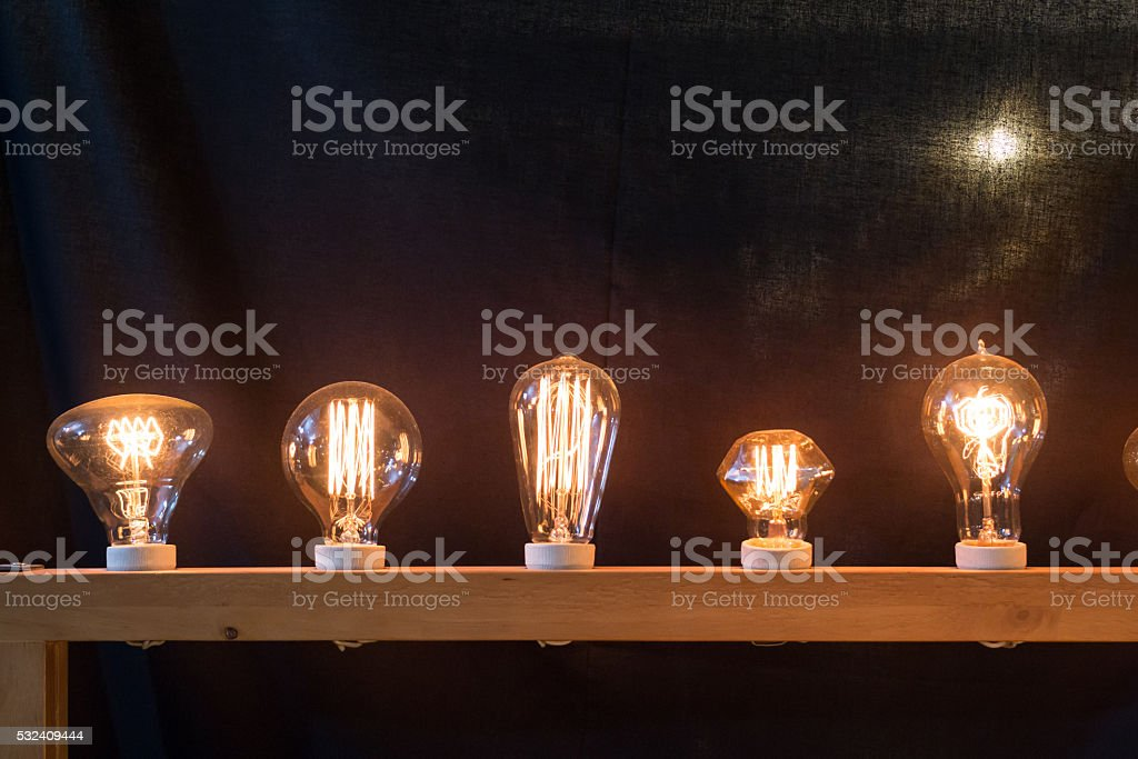 Сияющий желтый дизайн лампочки в черный фон Стоковые фото Стоковая фотография