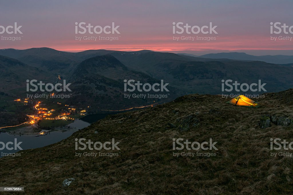 Glowing backpacking tent on side of mountain overlooking valley. stock photo