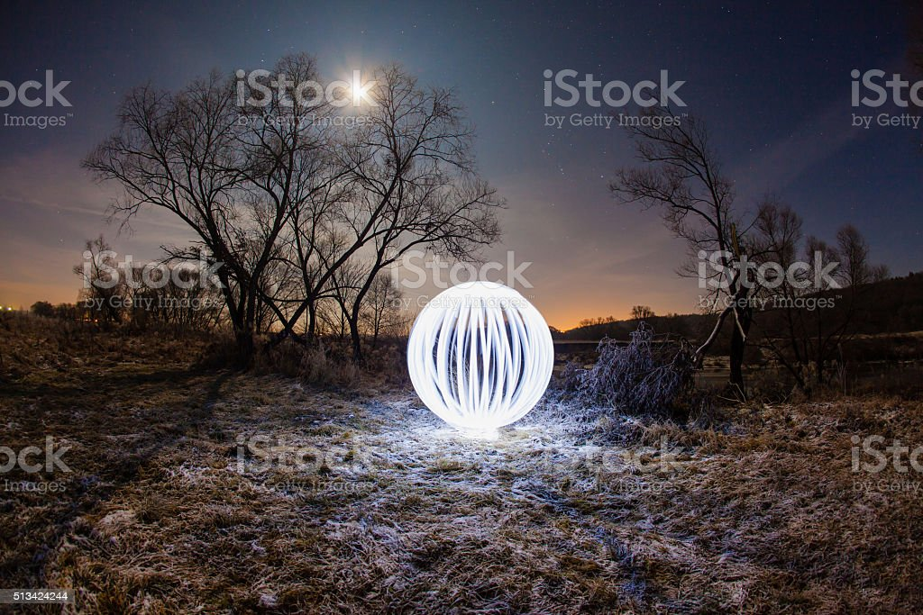 Glowing ball between the trees stock photo