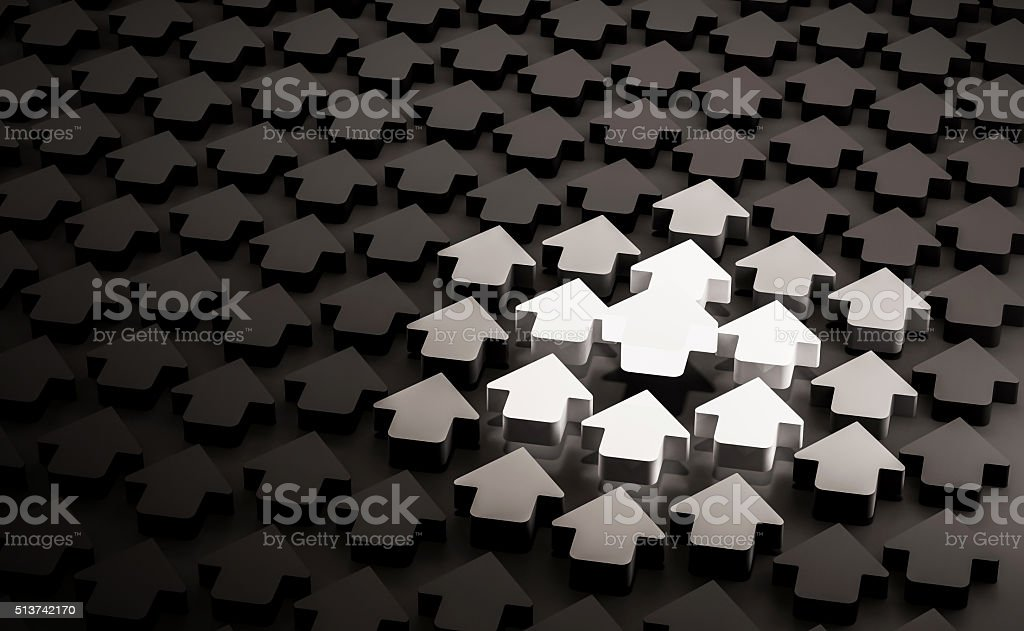Glowing bright arrow in group of black arrows stock photo