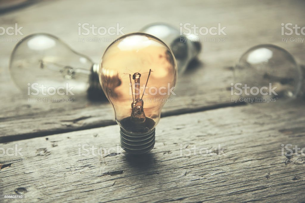 glowing bulb uniqueness concept on brown wooden table stock photo
