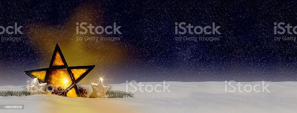 glowing Christmas star by night with snow stock photo