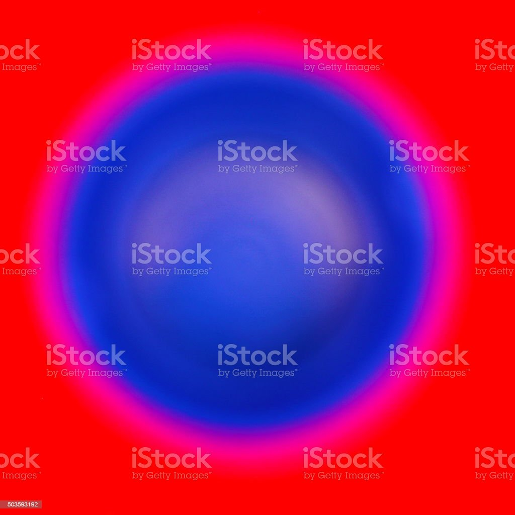 Glowing Deep Blue Ringed Sphere on Red Square Background stock photo