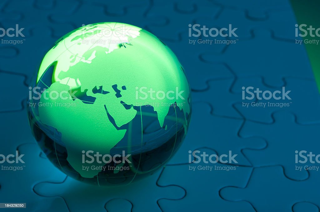 Glowing green globe on a blue jigsaw puzzle royalty-free stock photo