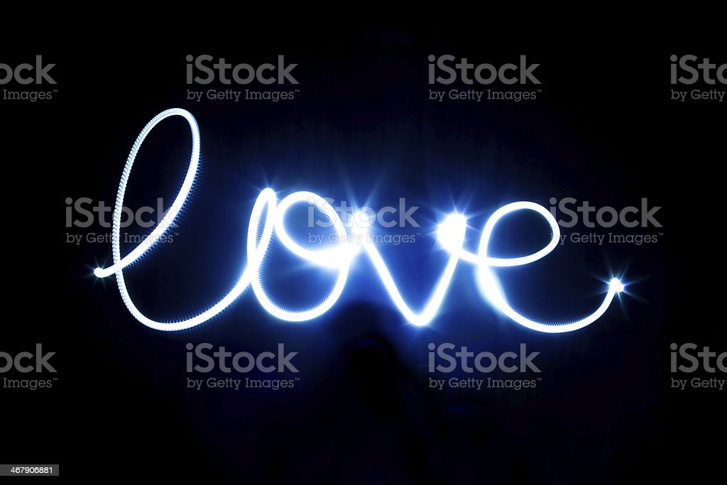 Glowing inscription LOVE on a black stock photo
