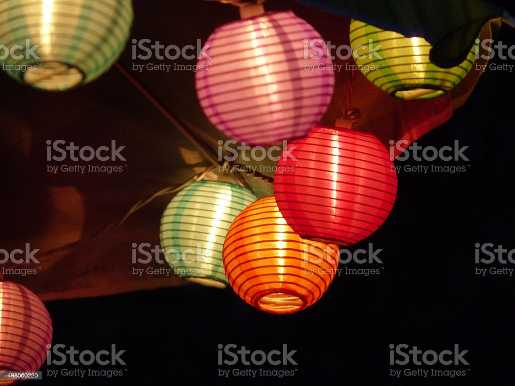 Glowing Japanese Lantern Style String Lights on Outdoor Umbrella stock photo