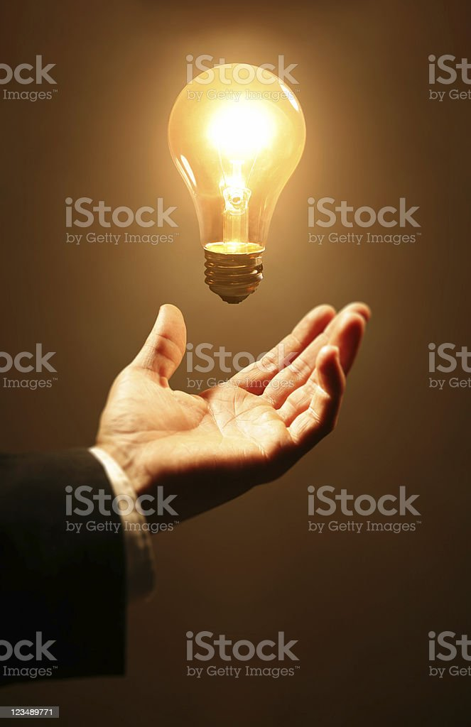Glowing light bulb above a man's hand stock photo